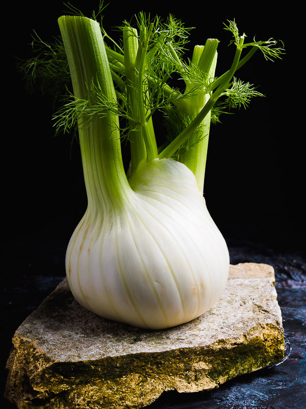 Fresh fennel on a old brick and a black textured table. Finocchio fresco su mattone e tavolo nero ruvido.