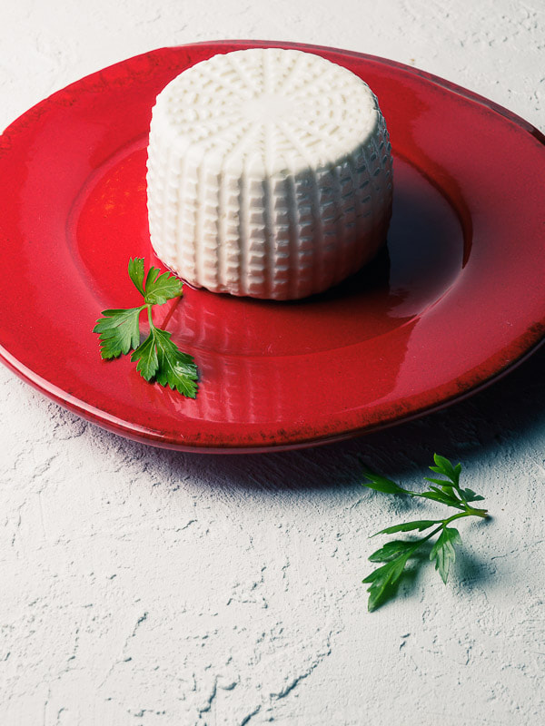 Small ricotta on red dish with parsley on white textured table. Ricottina fresca su piatto smaltato rosso con prezzemolo su tavolo bianco ruvido