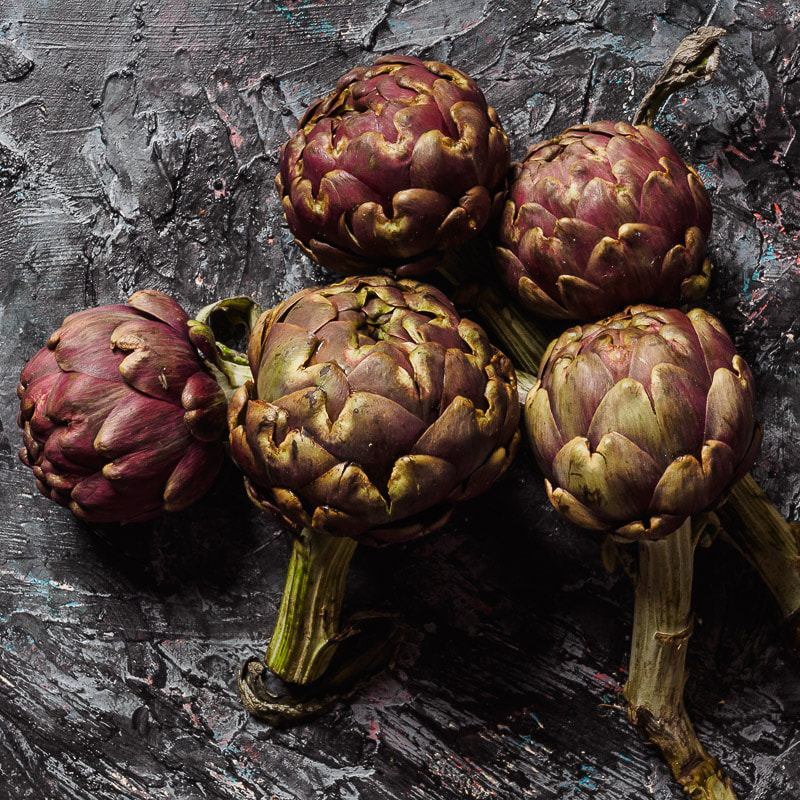 Gruppo di carciofi romani con gambo su tavolo nero ruvido. Group of artichokes on black textured table.