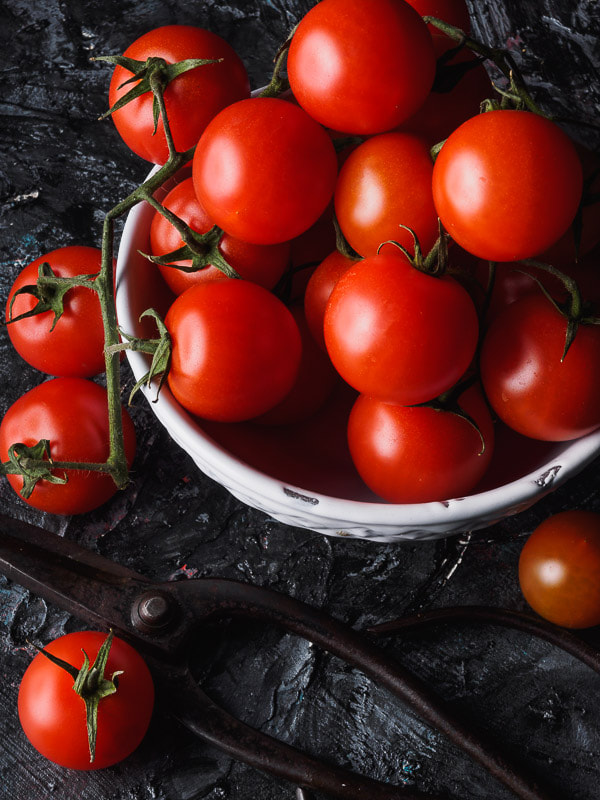 Pomodori ciliegino in un a ciotola bianca su tavolo nero ruvido e forbice da giardino di ferro. Round tomatoes  in a white bowl on a black textured table and an iron scissor.